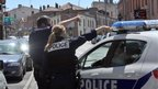 French police stand and point near the CIC bank in Toulouse