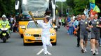 Vicki Dillon carries the Olympic flame through Carlisle