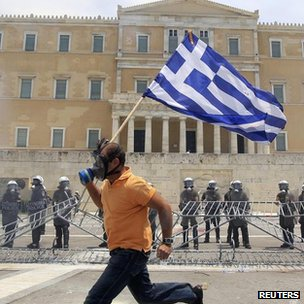A demonstrator with a Greek flag runs in front of the parliament in Athens. File photo