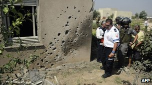 An Israeli paramedic and border police survey the damage caused by a rocket launched from the Palestinian Gaza Strip and which hit the Saad Kibbutz in southern Israel on Wednesday