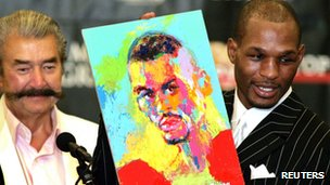 Boxer Bernard Hopkins holds up a portrait of himself painted by artist LeRoy Neiman