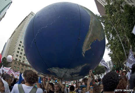 Demonstrators hold up an inflatable globe during a march at the Rio summit