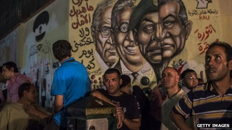 Egyptian men look on at graffiti of ousted Egyptian President Hosni Mubarak 