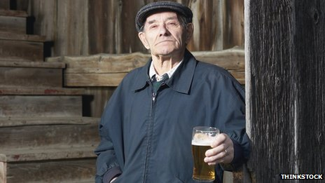 Old man holding a pint of beer