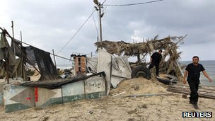 Members of Hamas's security forces walk on a Hamas compound damaged after an Israeli air strike in the northern Gaza Strip on 20 June 2012