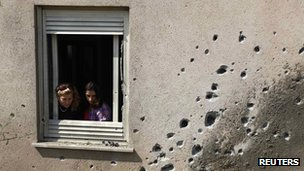 Israeli women look out the window of a house damaged after a rocket fired by Palestinian militants in Gaza landed in Kibbutz Sa'ad outside the central Gaza Strip 20 June 2012
