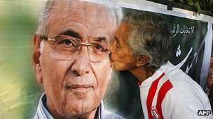 A supporter of Mr Shafiq kisses a poster bearing his image