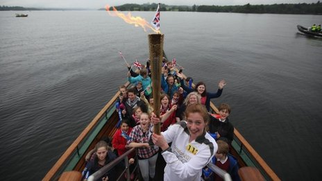 Triathlete Stephanie Booth, 15, with the Olympic flame and school children on board the Tern steam boat on Windermere, 21 June 2012