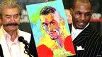 Boxer Bernard Hopkins holds up a portrait of himself painted by artist LeRoy Neiman
