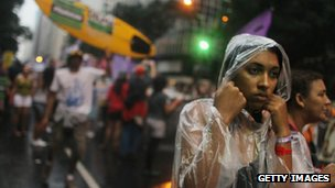 Environmental supporters march in the rain while protesting the first day of high-level talks at the Rio + 20