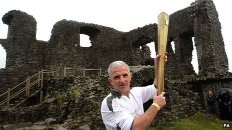 Torchbearer Michael Liptrot with the Olympic flame at Kendall Castle
