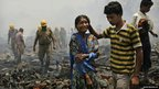 A woman is comforted by a relative while walking in the remains of a shanty town after a major fire in New Delhi, India