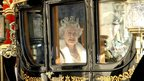 Queen Elizabeth II in a horse drawn carriage on route to the State opening of Parliament