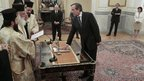 Newly appointed Greek Prime Minister Antonis Samaras is sworn in as President Karolos Papoulias (centre rear) attends the ceremony at the presidential palace in Athens 