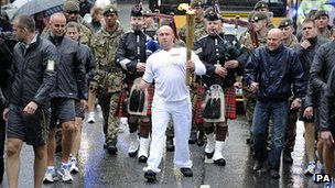 Dave Watson carries the Olympic Flame on the Torch Relay leg through Lancaster