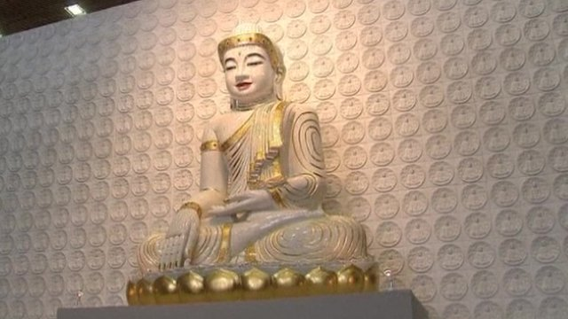A statue of Buddha in the main prayer room of the temple