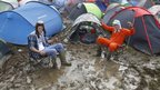 Festival-goers sit in the mud at the campsite at the Isle of Wight festival