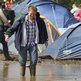 A festival-goer walks through the water and mud at the campsite at the Isle of Wight festival