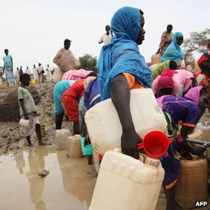 People gathering water at a man-made water hole, in South Sudan's Upper Nile state