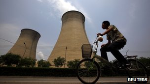 A man rides his bicycle past the cooling tower and chimneys from a coal-burning power station in Beijing