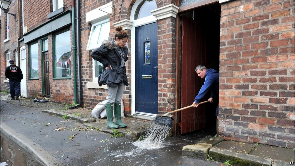 A man clears flood water from