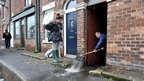 A man clears flood water from his house in Croston, Lancashire, after the river Yarrow burst its banks