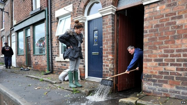 Tom Burke clears flood water from his house in Croston, Lancashire