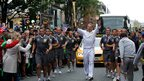 Sir Chris Hoy, a four-time Olympic gold medallist in cycling, carries the Olympic torch through the streets of Manchester