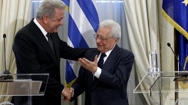 Newly-appointed Greek Foreign Minister Dimitris Avramopoulos (left) shakes hands with outgoing Foreign Minister Petros Molyviatis