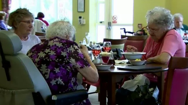 Elderly people having a meal