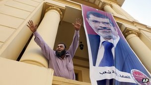 A supporter of Egypt's new president celebrates at Mohammed Mursi's campaign HQ in Cairo
