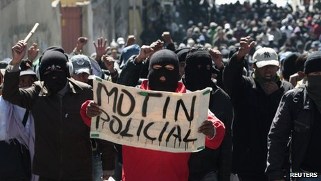 "Police officers hold up a sign saying ""police mutiny"" at a demonstration in la Paz on 24 June 2012"
