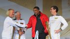 Leigh Francis, aka Keith Lemon, meeting former Olympian Daley Thompson alongside torchbearer Robin Money (L) and Gil Steyaert (R)