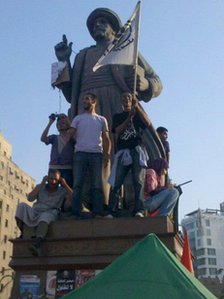 People stand on statue in Tahrir Square, Egypt. Photo: Ali Tobah