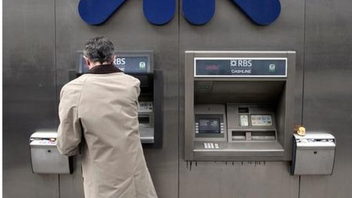 A man uses a Royal Bank of Scotland (RBS) cashpoint