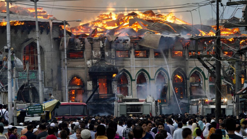 Crowds watch as firefighters try to extinguish a fire engulfing a 200-year-old Sufi shrine in Srinagar.