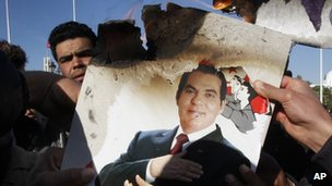 Protestors burn a photo of former President Zine El Abidine Ben Ali during a demonstration in Tunis, Tunisia