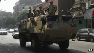An Egyptian military police armoured personnel carrier patrols a street in Cairo