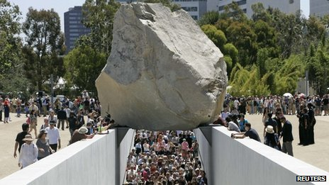 People walk under Michael Heizer's Levitated Mass artwork in LA