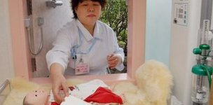Nurse reaches for a prosthetic baby in a 'baby hatch' in Japan
