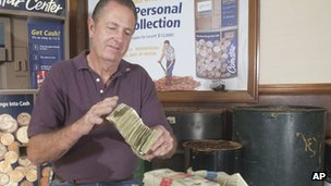 Edmond Knowles counting notes in exchange for over 1.3 million pennies in 2005