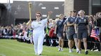 Teresa Loney carries the Olympic Flame on a lap around the playing field of Morley High School