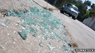 Broken glass on the road, with car in the approaching in the background