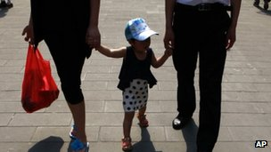 A couple holds the hands of its child as they walk down a street in China&#039; s capital Beijing in May 2012