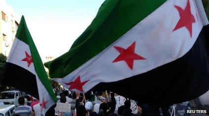 Protestors waving large Syrian flags