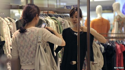 A customer tries a dress in front of a mirror at a shopping mall in Nanjing, Jiangsu province May 29, 2012