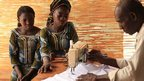 Two women watching a man doing tailoring work in Burkina Faso