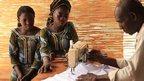 Two women watching a man doing tailoring work in Burkina Faso