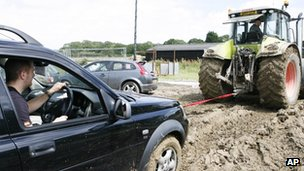 A tractor towing a car