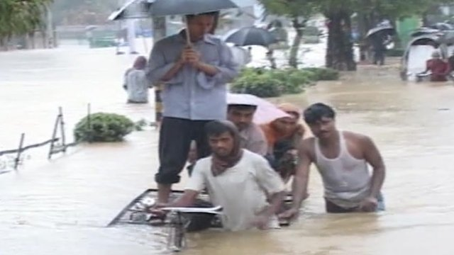 People in Bangladesh walking through floodwater